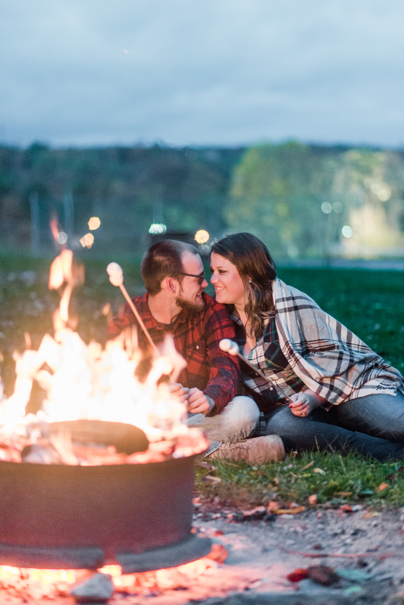 Fall engagement session by camp fire in Granite Hill Camping Resort