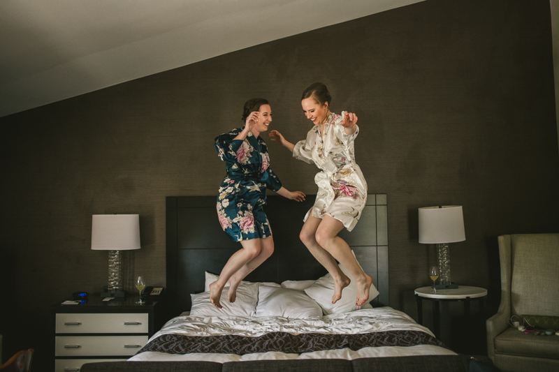Industrial chic April wedding bridal party jumping on a bed in Baltimore City's Radisson Hotel by Britney Clause Photography