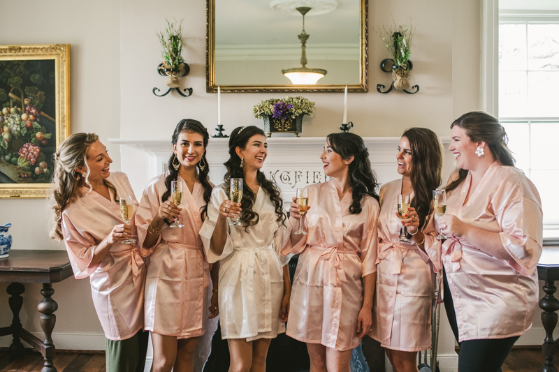 A beautiful stormy April wedding at Springfield Manor in Thurmont Maryland bridesmaids cheers with custom robes and champagne