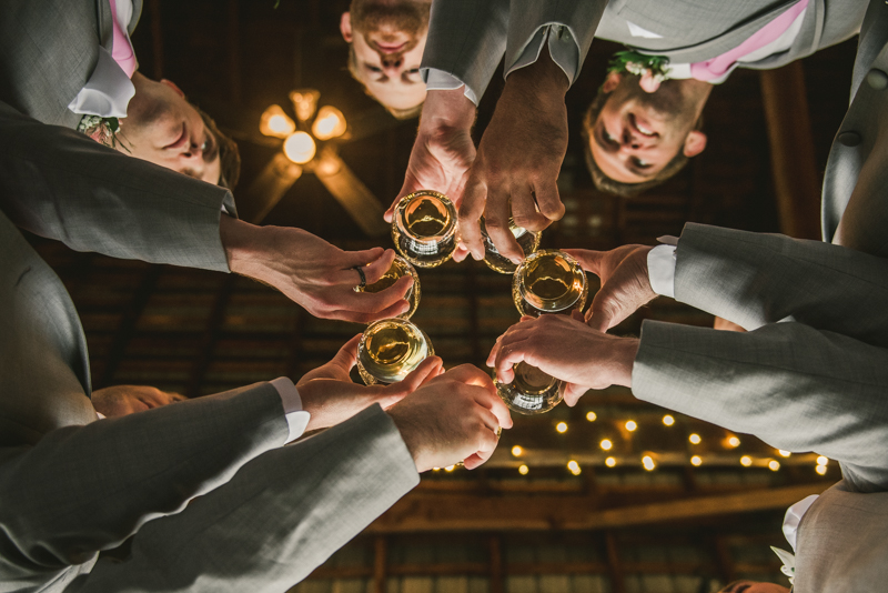 A beautiful stormy April wedding at Springfield Manor in Thurmont Maryland groomsmen cheersing in a barn
