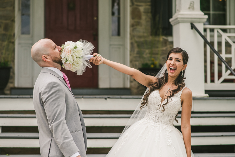 A beautiful stormy April wedding at Springfield Manor in Thurmont Maryland bride and groom portraits with bouquet in grooms face