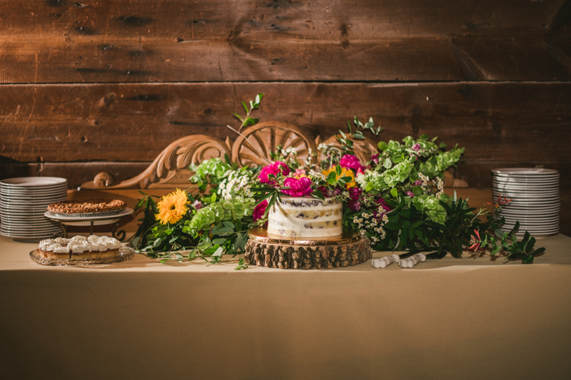 Gorgeous summer wedding reception details using farmhouse tables and Sungold Flower Co florals at Rocklands Farm Winery in Poolesville, Maryland by Britney Clause Photography a husband and wife wedding photographer team in Maryland