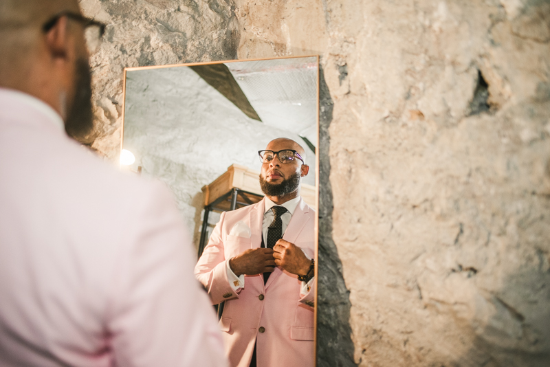Handsome groom getting ready in Main Street Ballroom's groom suite in Ellicott City by Britney Clause Photography