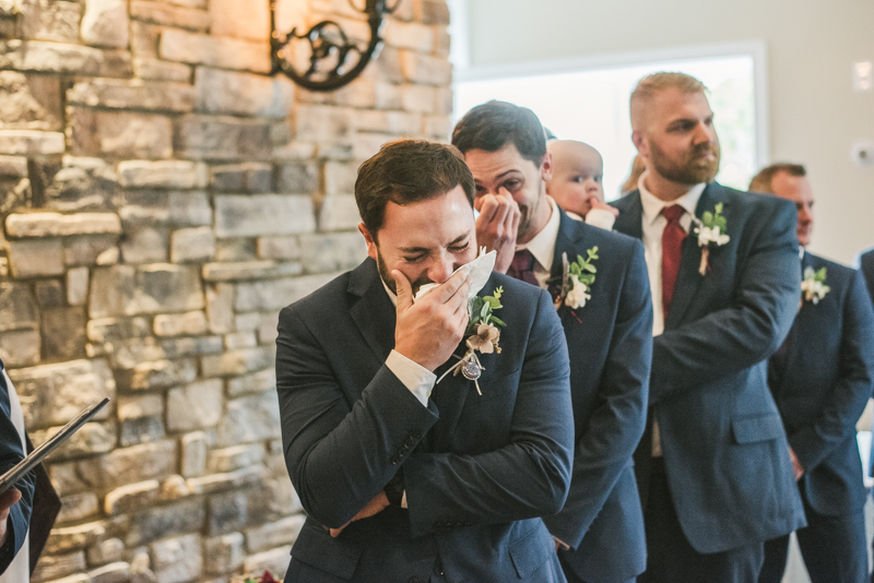 An emotional groom waiting for his bride at the end of the aisle at Kurtz's Beach in Pasadena, Maryland. Photo by Britney Clause Photography